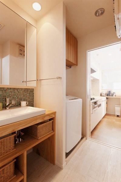 洗面所 オープン収納のある洗面カウンターはアッシュフリー板で造作らしい 洗濯機の上にも吊り戸棚 収納棚の扉はタモ材らしい