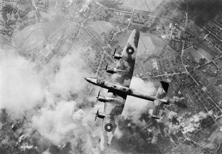 An RAF Handley Page Halifax Mk III bomber over an oil refinery target