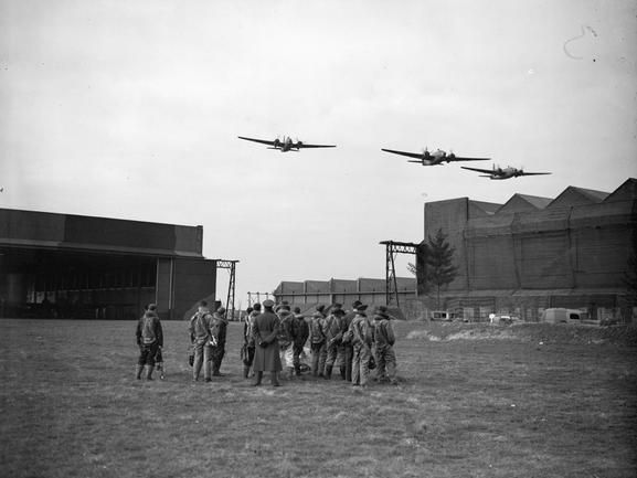 ROYAL AIR FORCE BOMBER COMMAND, 1939-1941.  Three Vickers Wellington Mark IAs of No. 149 Squadron RAF make a low pass over the hangars at Mildenhall, Suffolk, watched by a group of aircrew on the ground.