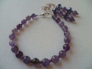 Noblesse, une jolie parure composée d'un bracelet monté sur fil câblé, fermoir mousqueton couleur argenté, perles en pierres naturelles d'améthyste et perles de rocaille. Longueur 22 cm. Longueur intérieure 19.5 cm.  Et d'une paire de boucles d'oreilles dormeuses, perles en pâte de verre et perles en pierres naturelles d'améthyste.