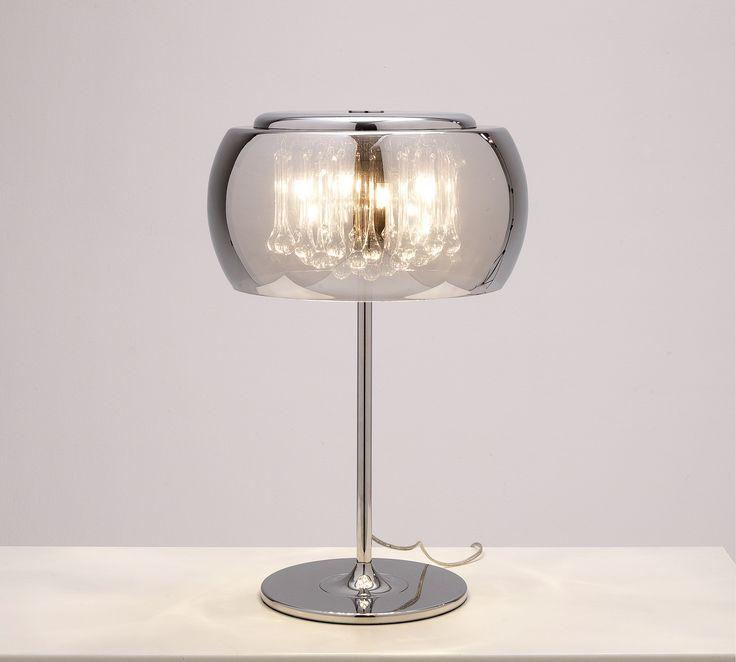 La danza dei materiali si esalta in questa lampada Stones da tavolo in metallo, vetro e specchio. Il color cromo e le linee curve e morbide fanno di questa lampada un dettaglio chiave di stanze da letto o soggiorni dal carattere soft e puro.