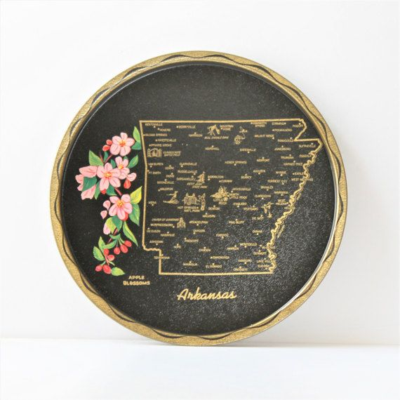 Bring back memories of childhood road trips when families picked up tin trays like this Arkansas tray as a vacation souvenir. The tray features a map of Arkansas, with key cities and local attractions highlighted in gold ink that pops against the black background. A spray of the state flower – apple blossoms – is shown in full-color beauty along the left side of the tray. The edge of the tray is in gold, with a wavy line of black. The tray is in great vintage condition without paint loss or…