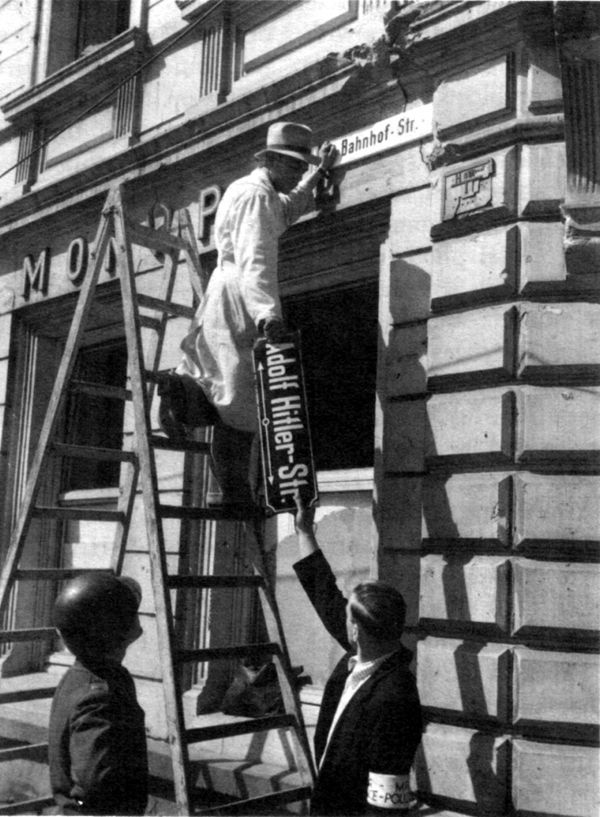 """Denazification in Germany: Workers removing the signage from a former """"Adolf Hitler Street"""""""