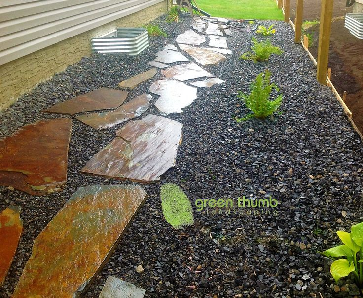 Creston Valley Flagstone path. Pulling a lawnmower through rocks is painfully frustrating. By adding a flagstone walkway you are creating an easy way to walk to the back yard and you no longer have to struggle with pulling a lawnmower though rocks.