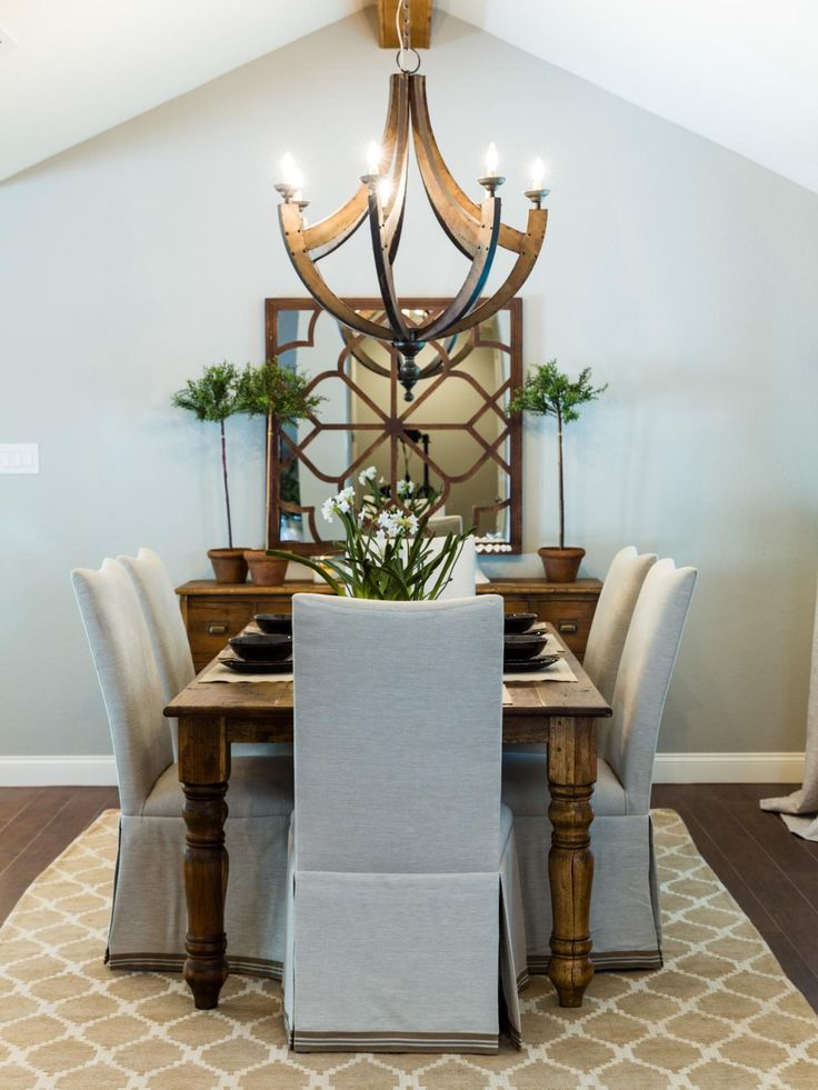 This neutral dining room, designed by Chip and Joanna Gaines, gets warm touches from rustic wood and burnished-metal features.