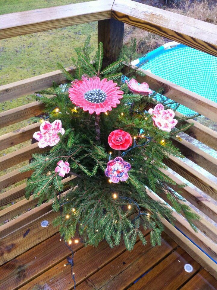Blommor i stengods på pinnar i kruka med granris.
