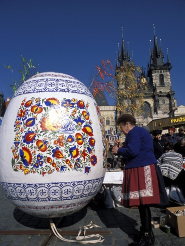 A woman paints a giant Easter egg at a traditional Easter market at the Old Town Square in Prague