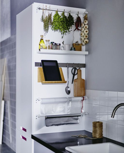 The side of a kitchen cabinet connected to a work top holds essentials like spices, scissors and a tablet stand