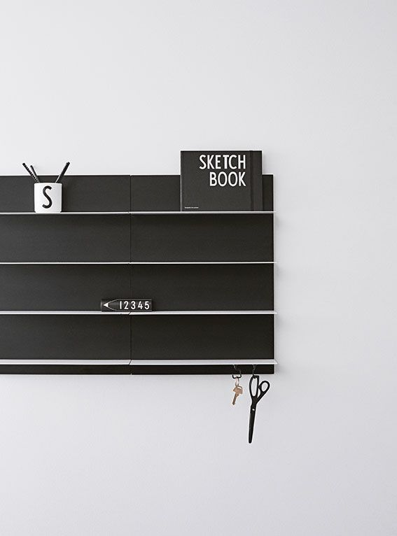 Home office with Black Paper Shelves. In a Scandinavian monochrome look. Functional notebook, crayons and porcelain cup with AJ Vintage ABC typography.
