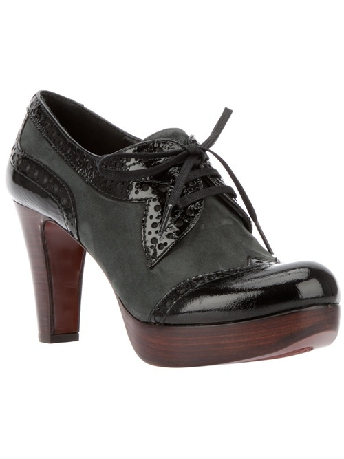Black leather pump from Chie Mihara featuring a patent leather toe with brogue detailing, a wooden platform, a leather sole, a tapered heel, brogue patent leather panelling at the sides and rear, and a front lace-up fastening.