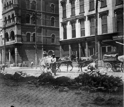 1907 - Main Street between 7th and 8th. Old Times Distillery Distributing Company and the Hartman Furniture and Carpet Company Warehouse