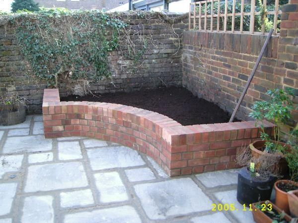 Raised brick garden bed tucks away in a corner. The curve is pleasing to the eye, and makes it easier to reach plants in the back. Garden bench seating.