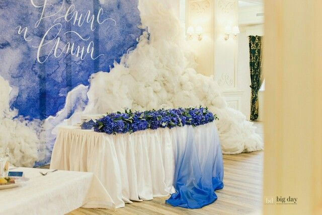 A sweetheart wedding table adorned with blue flowers and a blue tablecloth. The blue backdrop ties it all together beautifully in this wedding inspiration shoot!