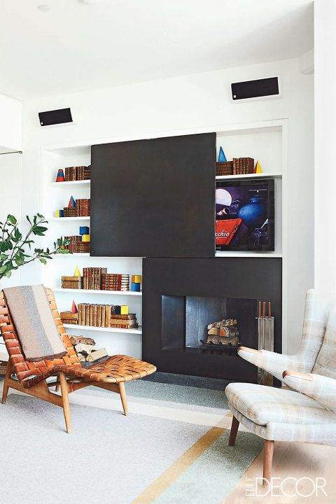 This fireplace surround, by Lee Mindel, features bookshelves and a sliding panel to hide a television.