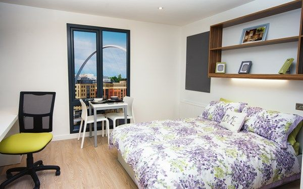 A studio room with a double bed, kitchen area and en-suite shower room.