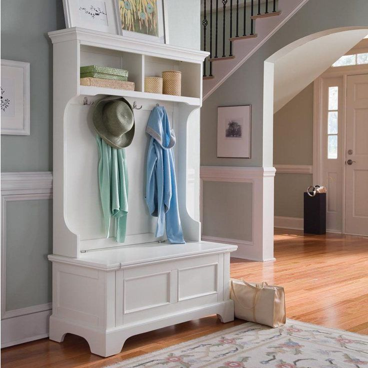 The Home Styles Naples White Hall Tree with Storage Bench  provides ample storage and organization with two open storage shelves,...