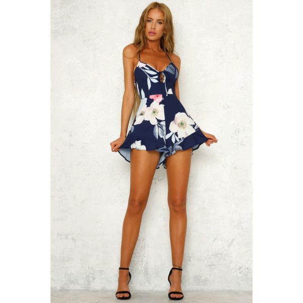 Navy playsuit. Partially lined. Cold hand wash only. Model is a standard XS and is wearing XS. True to size. Non stretchy fabric. No zipper, slip on style. Print placement may vary. Polyester. We know you'll LOVE our Lollapalooza Playsuit when festival season rolls around! This style has a tie up neckline, a lace up back detail and it has a partially elasticated waist so it's easy to slip into. It also has frill details on the shorts. Wear it with matte pink lipstick and silver earri...