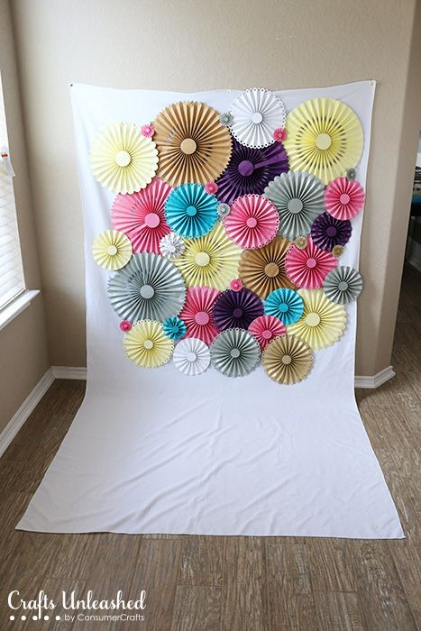 Make your photo DIY backdrop with this pretty paper rosette backdrop idea! The rosettes and backdrop is simple to assemble and it's perfect for any party!