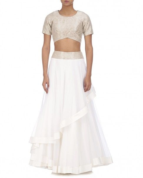 White brocade crop top featuring metallic beads embellishments all over. Short sleeves. Round neckline and asymmetric hemline. This set also includes a matching white horizontal skirt featuring beads embellished waist belt. Frilled panel adorns the front. Wash Care: Dry clean onlyClosure: Zip at side
