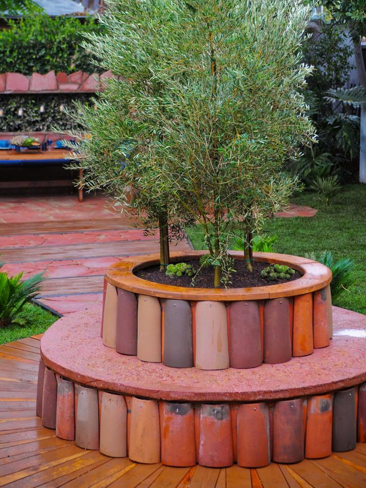 a barrel tile planter filled with bamboo becomes a focal point in this backyard garden