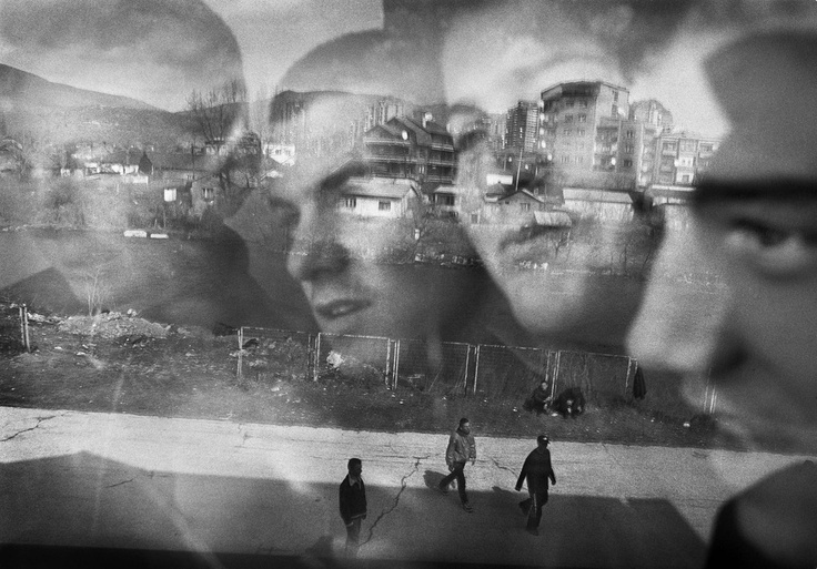 © Joachim Ladefoged - Albanian school children, in 2000, look out of a window in which is reflected the Serbian part of Kosovska Mitrovica, a city in northern Kosovo badly damaged during the 1999 Kosovo War.