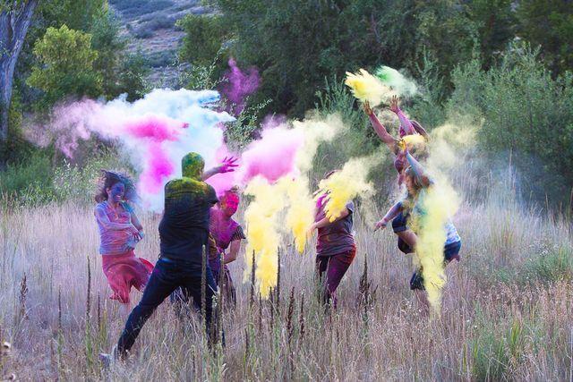 amigos aventandose polvo de colores en el campo