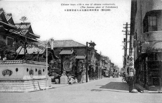 1935(昭和10)年ごろの横浜・中華街大通り入り口の絵はがき。手前には当時、小津安二郎が通った「安楽園」の広告も見える=横浜開港資料館所蔵