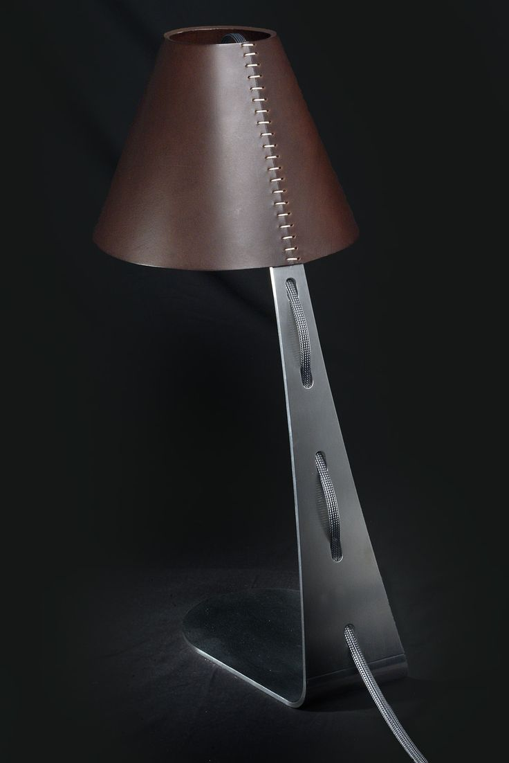 Table lamp, direct lighting, with a contemporary and elegant design. Available in two versions: 1) Steel- the structure is a bright or glazed steel, with visible cables on the lamp arm, lampshade in artistic Murano glass (pearl effect), or lampshade in leather. 2) Taylor- iron structure, hand sewed. The lampshade and structure of this lamp are entirely covered in leather