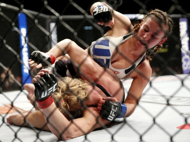 Miesha Tate, right, dominates Holly Holm during their UFC 196 title fight.