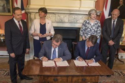 DUP MP Jeffrey Donaldson and Tory Chief Whip Gavin Williamson sign the deal in Downing Street watched by Arlene Foster, her deputy Nigel Dodds, Theresa May and First Secretary of State Damian Green. Picture: Getty