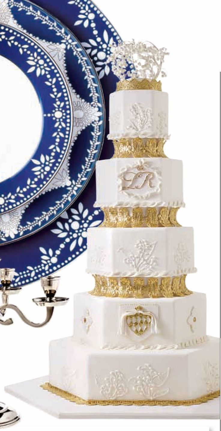 I decided to use hexagon shaped cake tiers to give the wedding cake a more architectural look, and I added 3 spacers for height. Each fondant-covered spacer was surrounded by gilded gum paste acanthus leaves. Royal wedding cakes traditionally feature their coat of arms; I came up with a simplified 3-D version of the Monaco Coat of Arms in white and gold. I also added a small sugar crown at the top to serve as a base for a spray of Lily of the Valley, which I handcrafted from sugar. Princess…