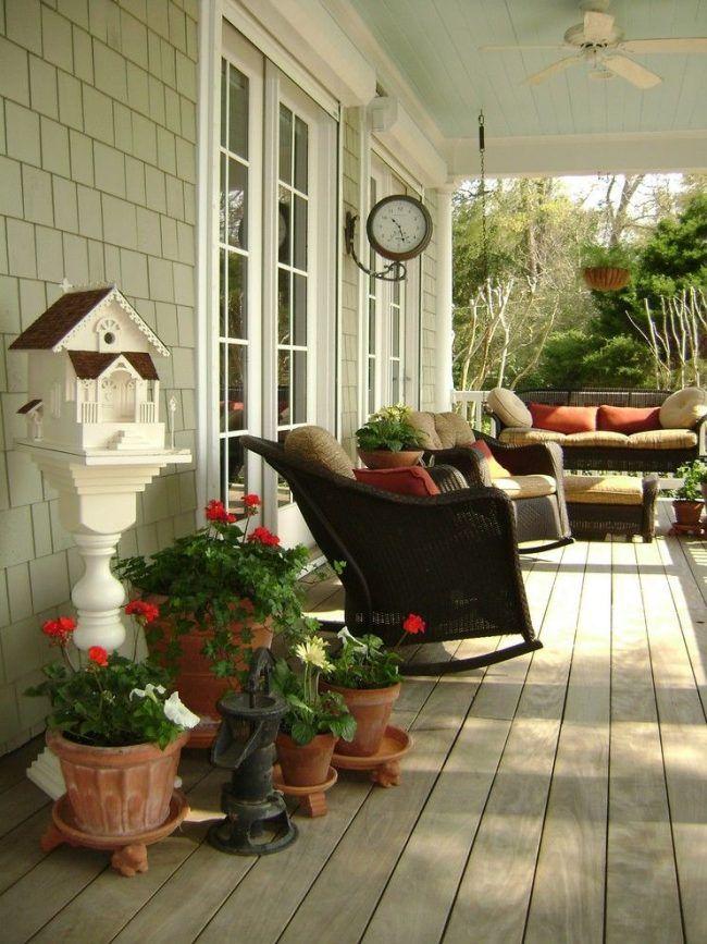 Деревянный сайдинг в оформлении террасы контрастирует с глиняными горшками с геранью. Плетеная мебель, фарфоровые и металлические детали завершают дизайн одноэтажного дома с террасой