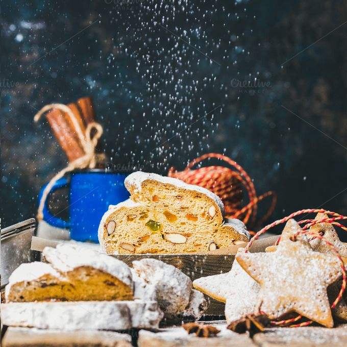 #Traditional German Christmas cake  Piece of Traditional German Christmas cake Stollen with festive gingerbread star shaped cookies and falling sugar powder selective focus dark blue grunge background copy space square crop