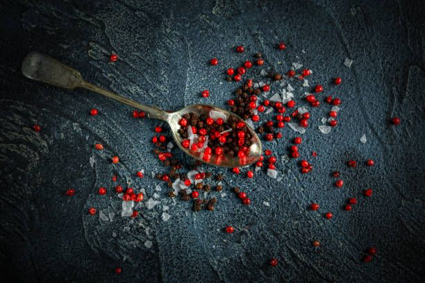 black red peppercorns mixed with salt on old rustic spoon