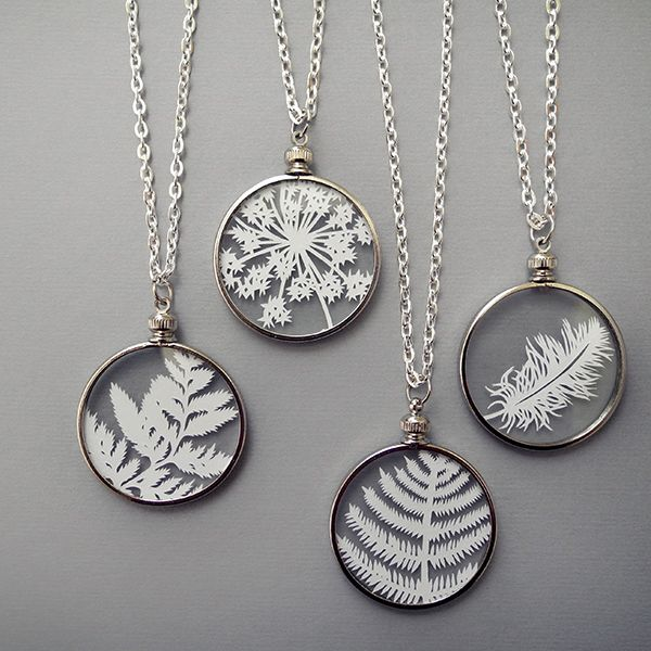 "Handcut paper feathers and leaves encased between 2 micro-thin pieces of glass.  Cut by hand with an x-acto knife and ready to wear with a 24"" silver chain.  By Sarah Trumbauer on Etsy"