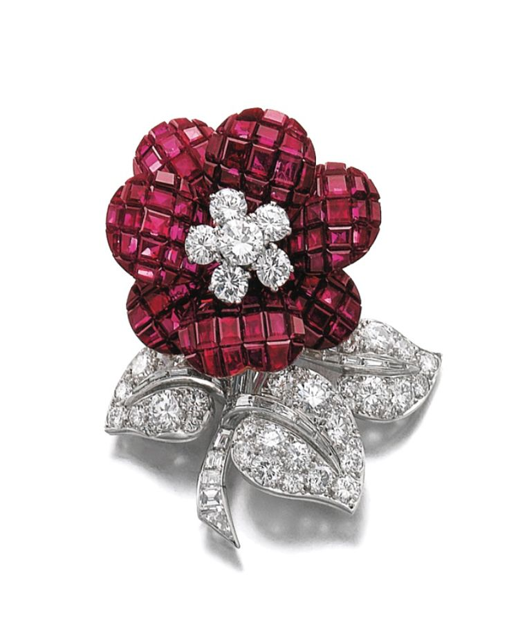 RUBY AND DIAMOND CLIP, VAN CLEEF & ARPELS, CIRCA 1955 Of floral design, the petals composed of calibré-cut rubies set en serti mysterieux, the pistils, leaves and stem set with circular-cut and tapered baguette diamonds, signed Van Cleef & Arpels, numbered, French assay and indistinct maker's marks, case stamped Van Cleef & Arpels.