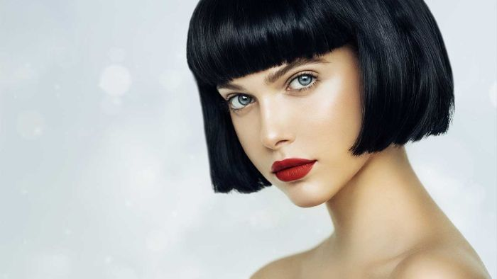 Woman With Pale Skin Black Hair Blue Eyes And Red Lips On A Light