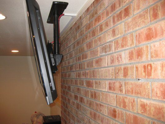 Ceiling Installation of a TV above a brick fireplace