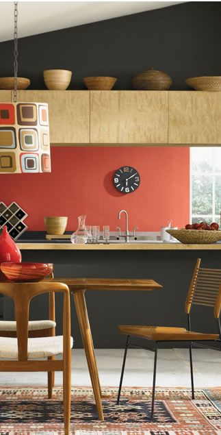 Coral back wall, wooden kitchen, anthracite walls, midcentury furniture. Yes please!
