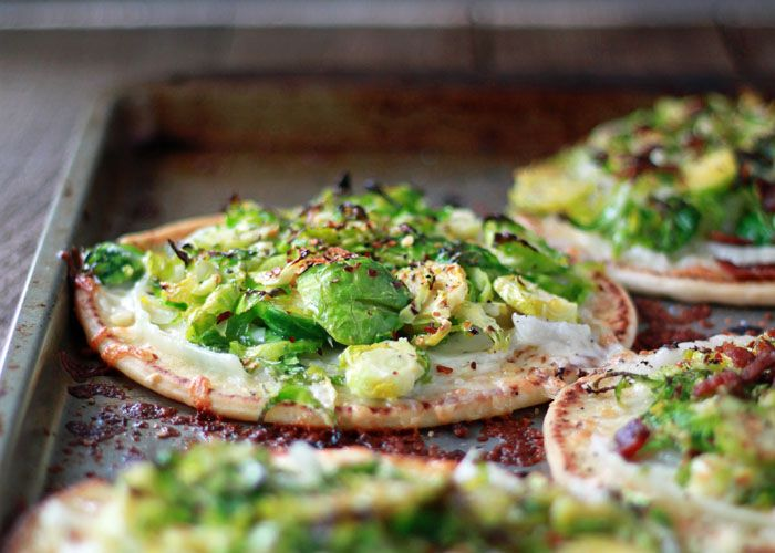Easy Brussels Sprouts Pita Pizza recipe - Assemble these delectable little pizzas in under 10 minutes. Vegetarian; just add bacon for the meat-eaters!