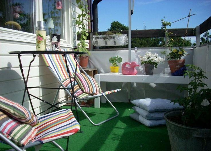 Klappmöbel mit bunten Kissen, Rasenteppich und Stoff Balkonbespannung