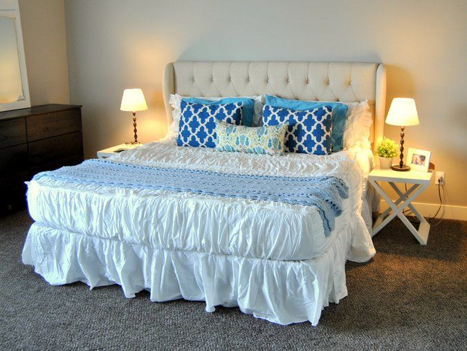 tufted upholstered king headboard white bedding blue pillows