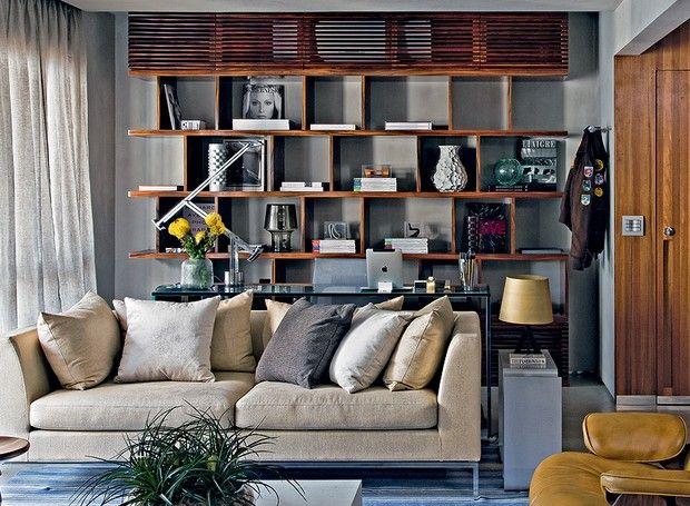 O arquiteto Diego Revollo fez a estante com pouca profundidade, para deixar tudo visível e decorar a sala. Na parte superior, um painel ripado esconde o ar-condicionado. Embaixo, a mesma solução foi usada para guardar documentos, pastas e impressora (Foto: Divulgação)