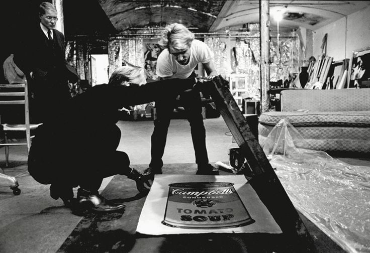Andy Warhol working with Gerard Malanga on silk-screening Campbells Soup Can paintings at The Factory (1965)