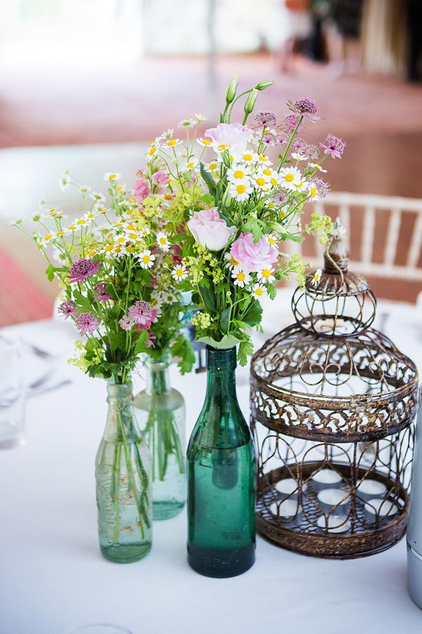 Daisies and wildflower table centre pieces with vintage bottles used as vases.