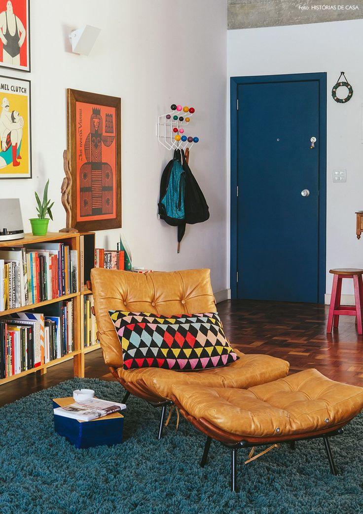 poltrona vintage de couro, porta pintada de azul e muitos livros em um apartamento dos anos 50 reformado pelos moradores, ambos arquitetos
