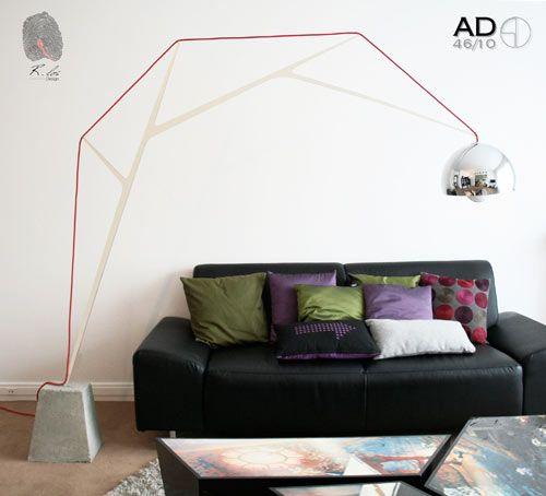 Romain Duclos' newest project is the AD46/10 lamp, an arched lamp that resembles a fishing rod. It is an homage to the famous Arco lamp and sits on a concrete base. The arch is angled and supported, and a red wire is used for playfulness.