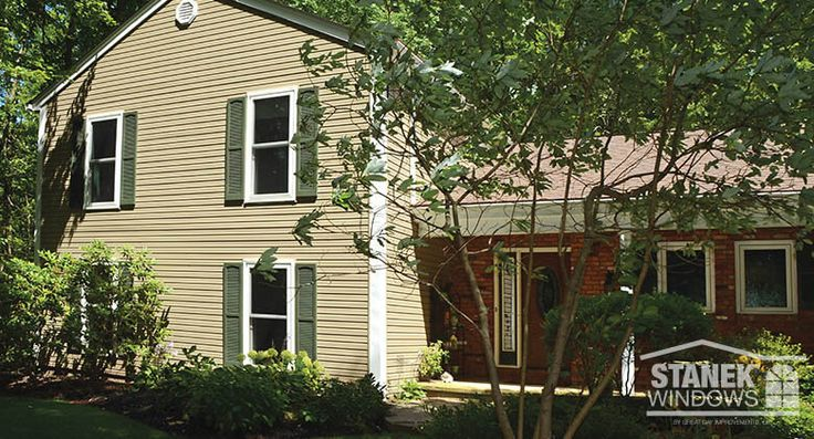 White, double-hung windows with hunter green shutters suit this home in the woods. Learn more.