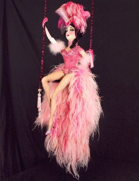 Mitzi, by Dustin Poche'  The ideal Ziegfeld Follies showgirl perched on her swing is a perfect picture in pink couture surrounded by blushed plumes and sequin top hat.  38 INCHES (7.62 CM) TALL