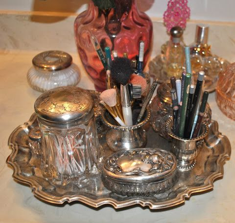 An old silver tray holds cosmetic sundries.